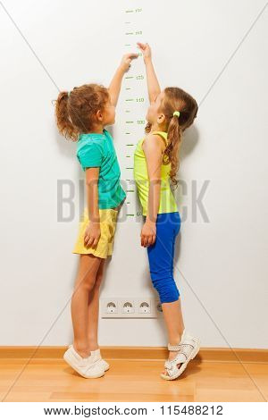 Two little girls standing by the wall and stretching hands on scale trying to reach high mark in full height portrait