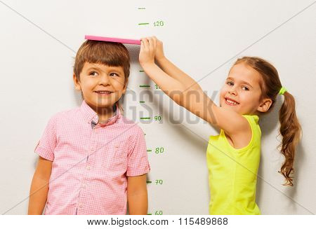 Little 5 years old girl measure a height of boy by scale on the wall
