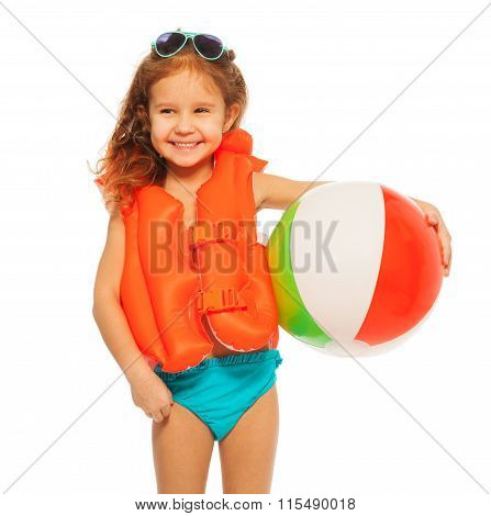 Happy smiling girl in sunglasses and orange lifejacket with colored rubber ball