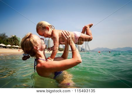 Side-view Mother In Sea Holds In Arms Small Daughter Smile