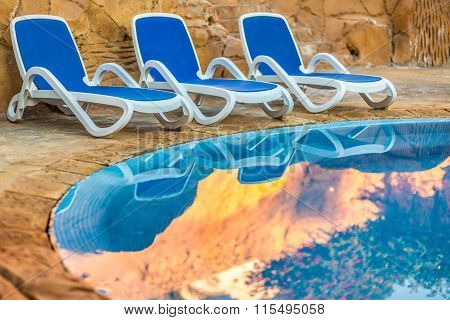 Three sunloungers reflected in blue water of the swimming pool