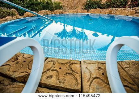 Closeup sunloungers and beautiful swimming pool with reflected of palm trees in a blue water, Egypt.