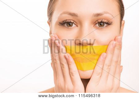Young girl taping her mouth.