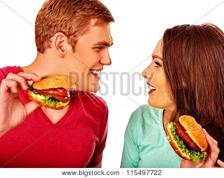 Young couple man and woman flirting and eating hamburgers  . Fastfood concept.  Isolated.