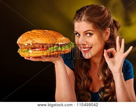 Girl holding big hamburger and showing ok gesture. Fastfood concept. Cheeseburger on foreground.