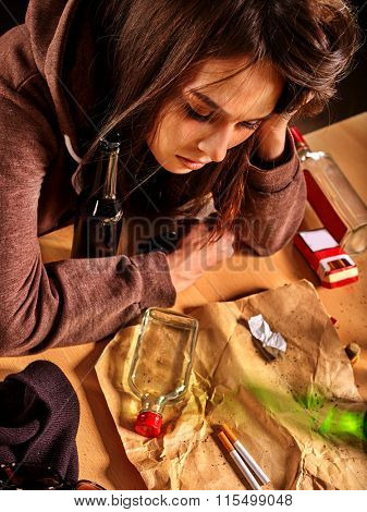 Girl in depression drinking alcohol and smokes cigarettes in solitude. Top view.