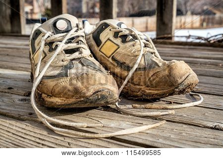 a pair of old muddy running shoes against wooden deck