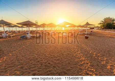 Beach with deck chairs and parasol during sunrise