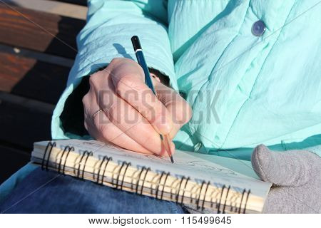 Drawing In A Notebook On The Waterfront