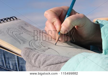 Drawing in a notebook on the waterfront. Sunny weather
