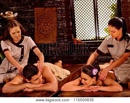 Loving couple  luxuriate  at oil Ayurveda spa treatment on wooden bed.
