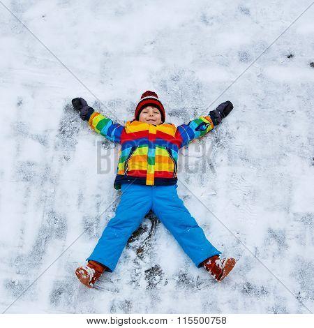 Little kid boy making snow angel in winter, outdoors