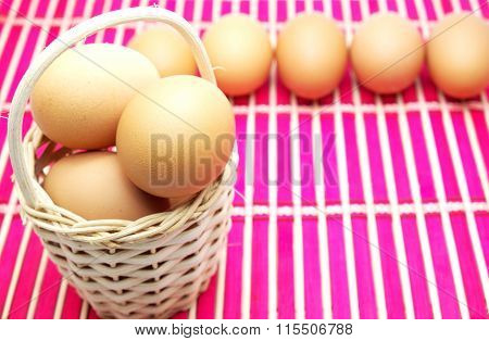 Eggs in/near wooden basket on pink bamboo mat. Focus on eggs in basket.