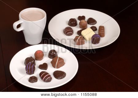Two Plates Of Chocolates With A Cup Of Hot Chocolate