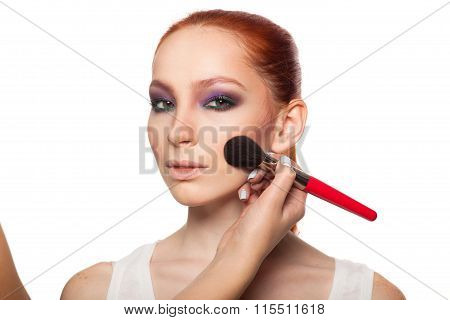 Professional Make-up artist doing glamour with red hair model makeup.  Isolated background.