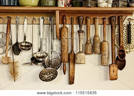 Different Kitchen Ware Hanging On The White Wall.