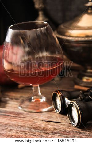 glass of cognac with binoculars and blue stained-glass candle