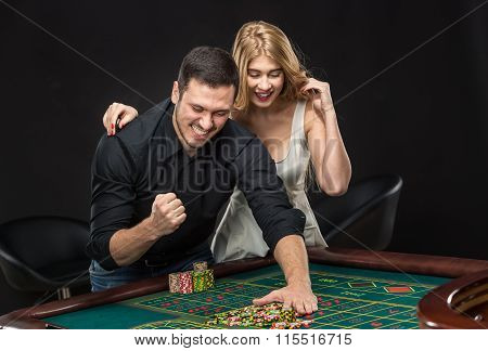 Young couple celebrating win at roulette table in casino.