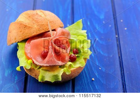 Fresh Yummy Hamburger With Ham, Lettuce And Whole Cranberries On Deep Blue Background Copyspace