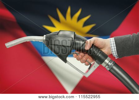 Fuel Pump Nozzle In Hand With National Flag On Background - Antigua And Barbuda