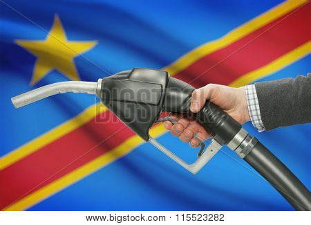 Fuel Pump Nozzle In Hand With National Flag On Background - Congo-kinshasa