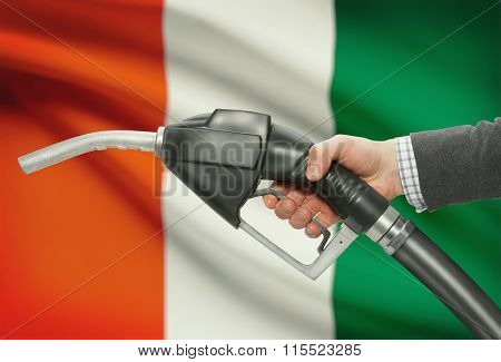 Fuel Pump Nozzle In Hand With National Flag On Background - Ivory Coast