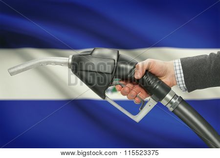 Fuel Pump Nozzle In Hand With National Flag On Background - El Salvador