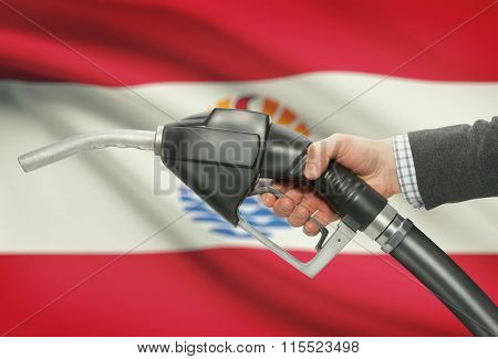 Fuel Pump Nozzle In Hand With National Flag On Background - French Polynesia