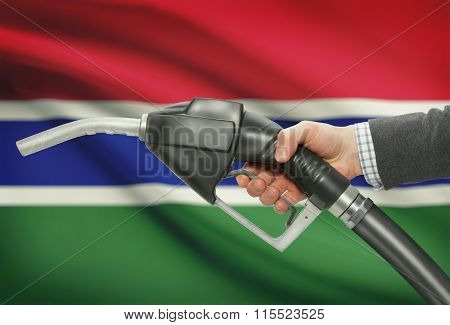 Fuel Pump Nozzle In Hand With National Flag On Background - Gambia