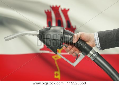Fuel Pump Nozzle In Hand With National Flag On Background - Gibraltar