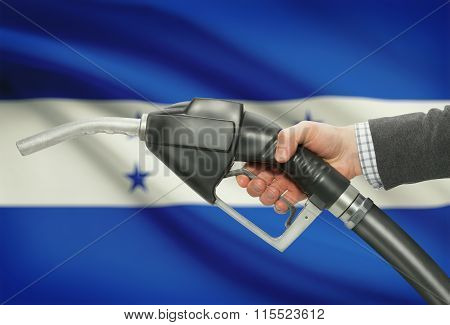 Fuel Pump Nozzle In Hand With National Flag On Background - Honduras