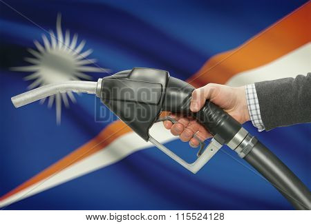 Fuel Pump Nozzle In Hand With National Flag On Background - Marshall Islands