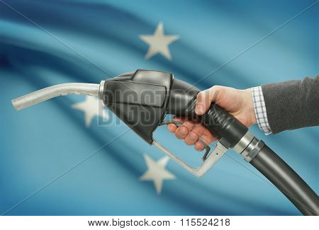 Fuel Pump Nozzle In Hand With National Flag On Background - Micronesia