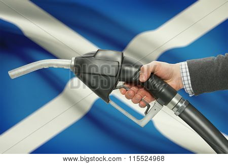 Fuel Pump Nozzle In Hand With National Flag On Background - Scotland