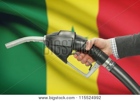 Fuel Pump Nozzle In Hand With National Flag On Background - Senegal