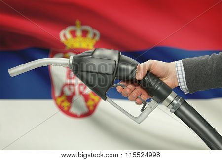 Fuel Pump Nozzle In Hand With National Flag On Background - Serbia