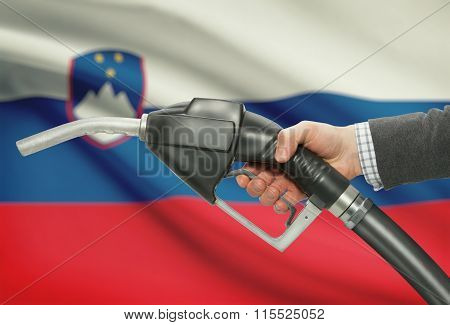Fuel Pump Nozzle In Hand With National Flag On Background - Slovenia