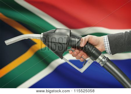 Fuel Pump Nozzle In Hand With National Flag On Background - South Africa