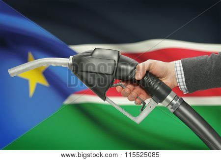 Fuel Pump Nozzle In Hand With National Flag On Background - South Sudan