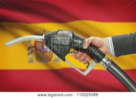 Fuel Pump Nozzle In Hand With National Flag On Background - Spain