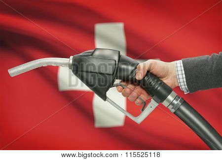Fuel Pump Nozzle In Hand With National Flag On Background - Switzerland