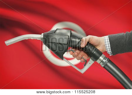 Fuel Pump Nozzle In Hand With National Flag On Background - Tunisia