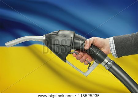 Fuel Pump Nozzle In Hand With National Flag On Background - Ukraine