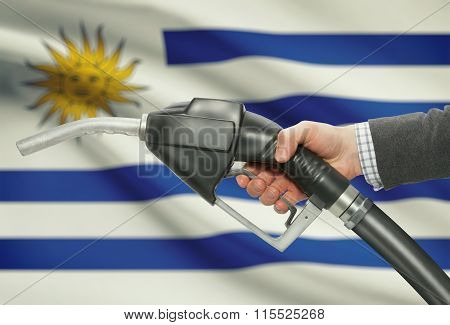 Fuel Pump Nozzle In Hand With National Flag On Background - Uruguay
