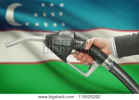Fuel Pump Nozzle In Hand With National Flag On Background - Uzbekistan