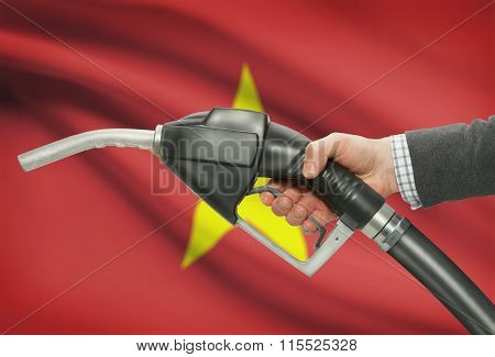 Fuel Pump Nozzle In Hand With National Flag On Background - Vietnam