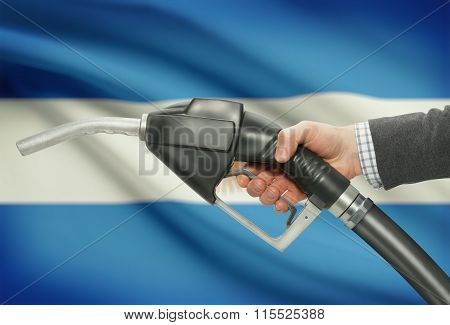 Fuel Pump Nozzle In Hand With National Flag On Background - Argentina
