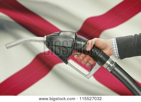 Fuel Pump Nozzle In Hand With Usa States Flags On Background - Alabama