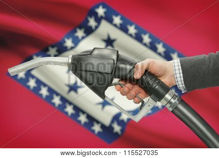 Fuel Pump Nozzle In Hand With Usa States Flags On Background - Arkansas