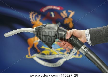 Fuel Pump Nozzle In Hand With Usa States Flags On Background - Michigan